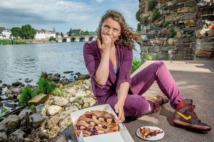 Culinair journaliste Laura de Grave, met streekproduct Limburgse vlaai van de Bisschopsmolen, langs de Maas in Maastricht met op de achtergrond de oude Maasbrug.