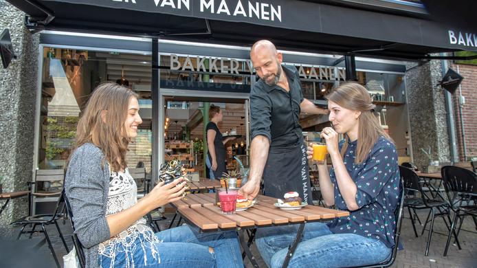 Vriendinnen Hanke Slotboom en Xanthe Verhoek eten een taartje op het terras van Bakkerij Van Maanen in Woerden.