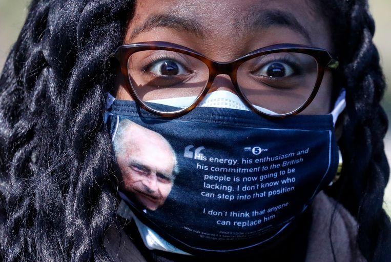 Een vrouw draagt een gezichtsbedekking met een foto van de hertog van Edinburgh terwijl zij langs de Long Walk in Windsor loopt.  Beeld AP