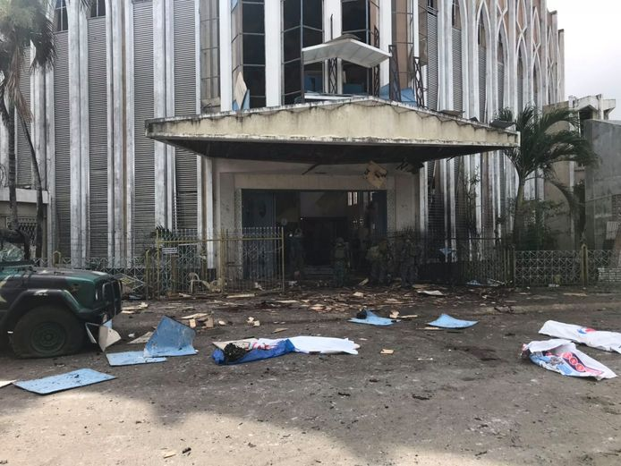 De ingang van de getroffen kerk. Bedekte lichamen op straat.