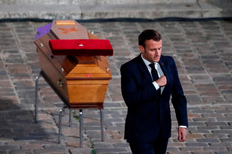 De Franse president Emmanuel Macron bewijst de laatste eer aan Samuel Paty. Op diens kist ligt de Légion d'Honneur, de hoogste Franse onderscheiding, die de president even daarvoor postuum heeft toegekend aan de door een fundamentalist vermoorde docent.    Beeld Francois Mori / POOL / AFP