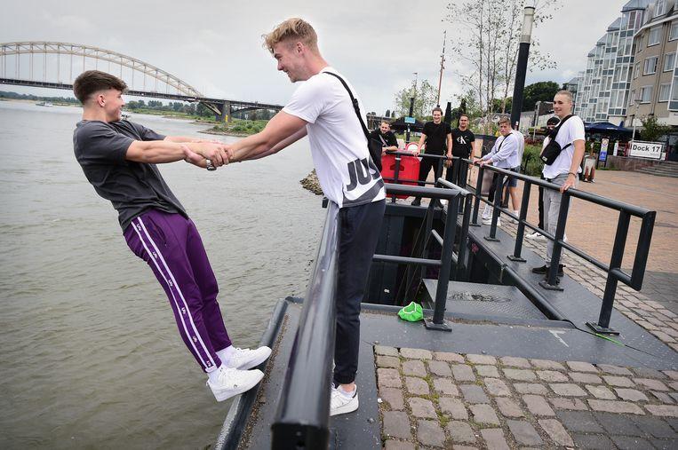 Nijmegen: Jongeren halen halsbrekende toeren uit onder elkaar aan de Waalkade.  Beeld Marcel van den Bergh