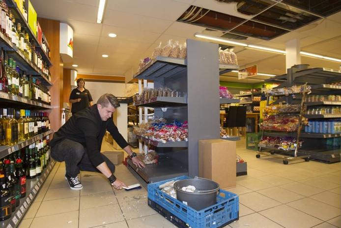 Exploitant Joost Peeters ruimt de schade in zijn winkel op.