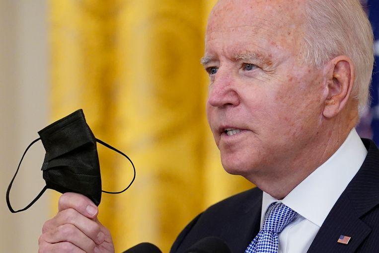 De Amerikaanse president Joe Biden houdt een mondmasker vast terwijl hij de nieuwe coronaregels voor ambtenaren uitlegt. (29/07/2021) Beeld AP