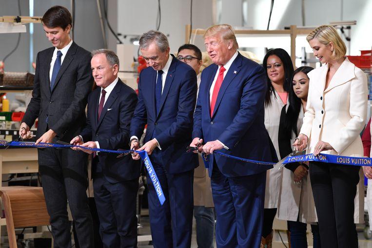 Ceo van LVMH Bernard Arnault (midden), opende vorige maand in aanwezigheid van president Donald Trump een werkplaats in de VS voor Louis Vuitton. Beeld AFP