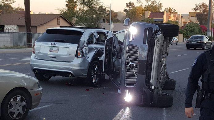 Een zelfrijdende Volvo ligt op zijn kant na een aanrijding.