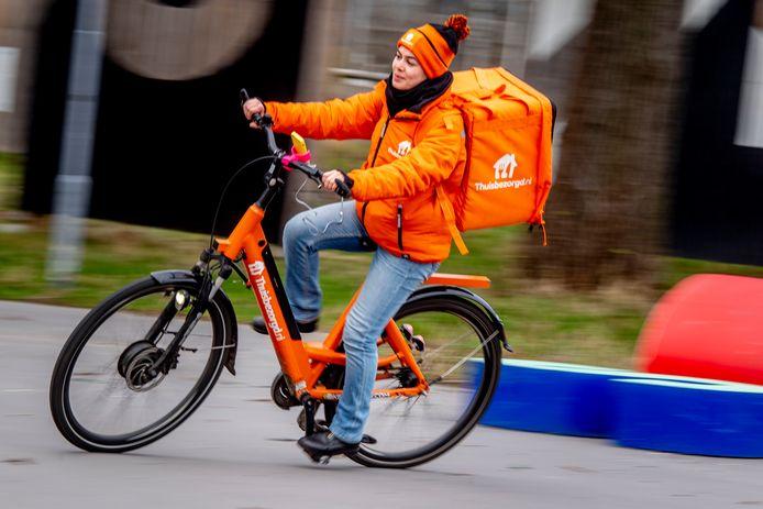 Een maaltijdbezorger van Thuisbezorgd.nl in actie. In tegenstelling tot Deliveroo zijn de koeriers van de Nederlandse concurrent wél in loondienst
