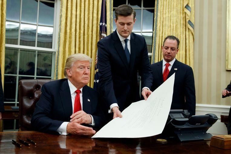 Rob Porter (m.), overhandigt Trump een document in het Witte Huis terwijl toenmalig stafchef Reince Priebus toekijkt. Beeld AP