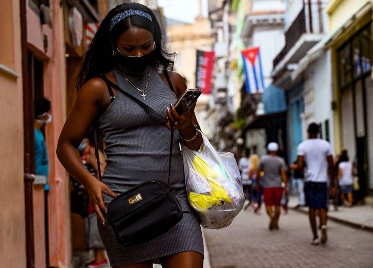 Een Cubaanse gebruikt haar telefoon op straat in Havana. Beeld AFP