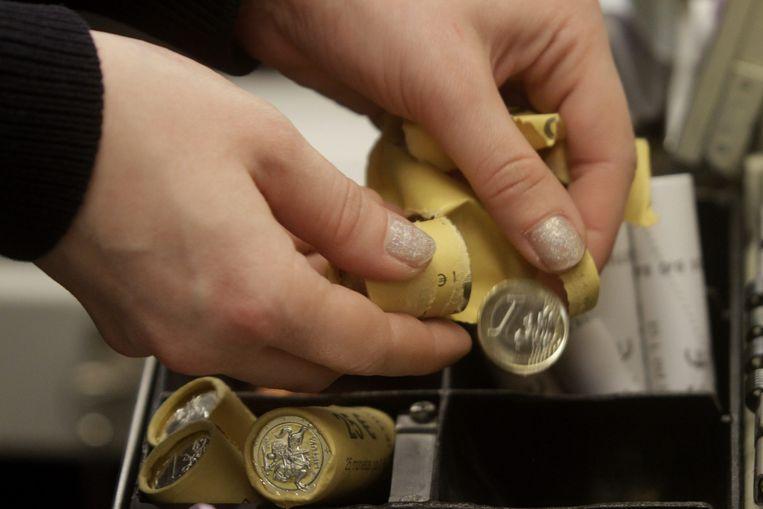Een kassamedewerker telt nieuwe euromunten uit Estland. Beeld EPA