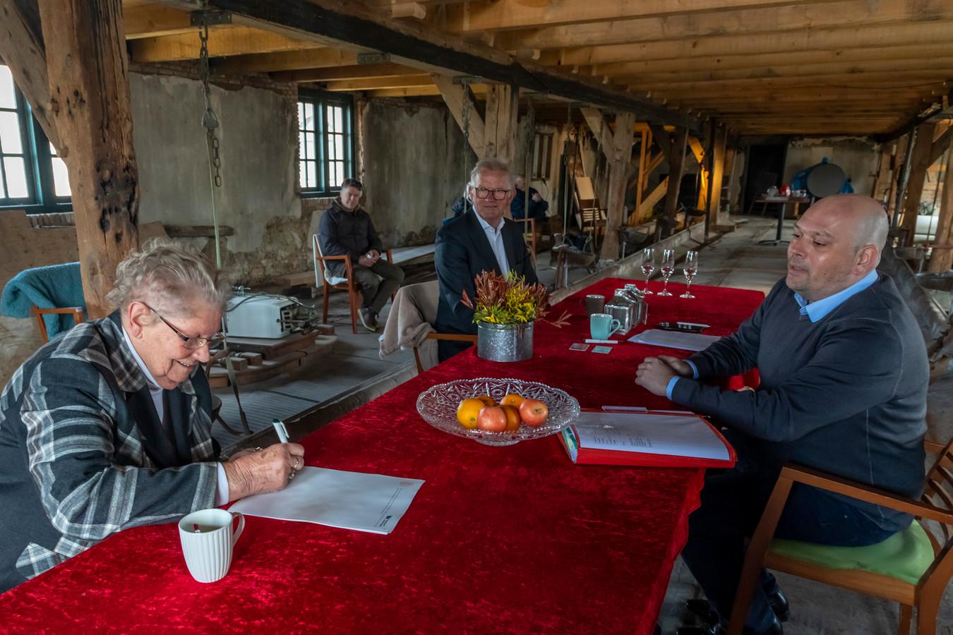 Gré Ruigrok tekent de papieren voor de overdracht. Theo Koot, penningmeester van de stichting Boerderij de Vlietwoning en notaris Paul Bols kijken toe.