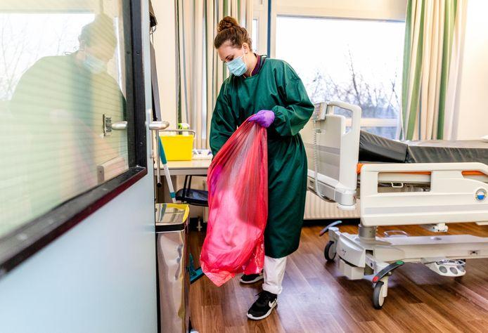 Een medewerker van het Albert Schweitzer ziekenhuis maakt een kamer schoon waar iemand heeft gelegen die besmet is geweest met het coronavirus.