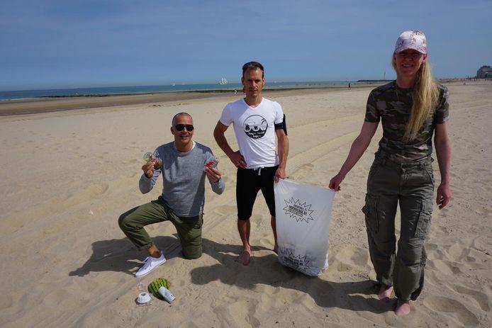 Tim Corbisier (centraal) van de Propere Strand Lopers en vrijwilligers Alexander en Katrien ruimen blikjes en bokalen op.