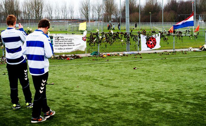 Clubleden bekijken op de dag van de uitvaart van grensrechter Richard Nieuwenhuizen de bloemen langs het veld van voetbalclub SC Buitenboys.