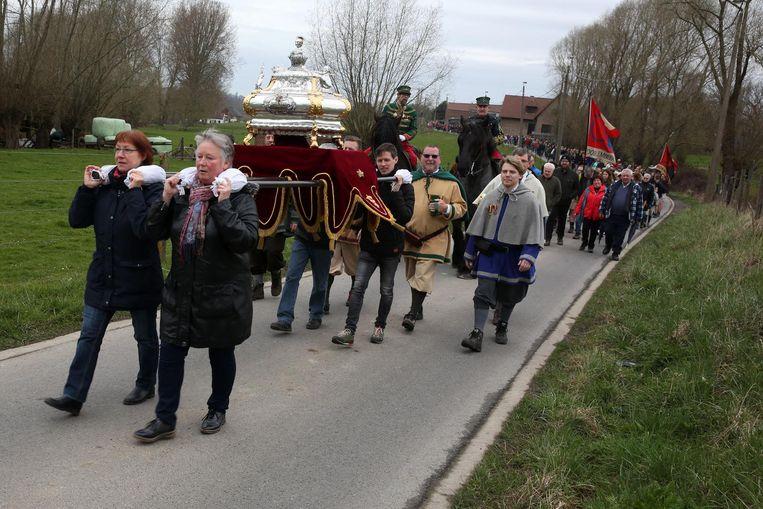 Het reliekschrijn van Sint-Veroon, gevolgd door een grote groep bedevaarders.