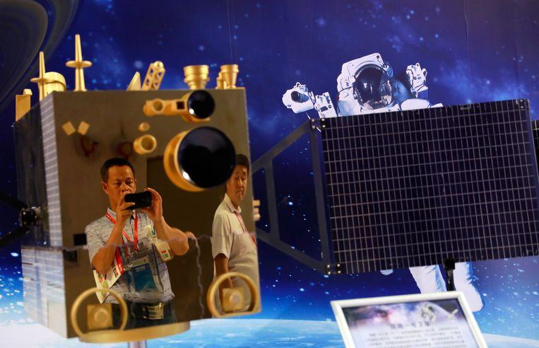 Een bezoeker neemt een foto van een nagebouwde satelliet op de Chinese Hightech Expo in Peking. Beeld EPA