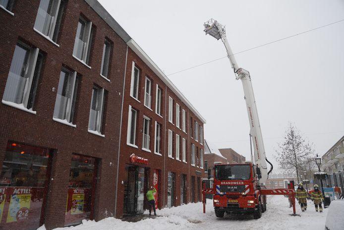 De brandweer haalt de sneeuw van het dak in Grave.