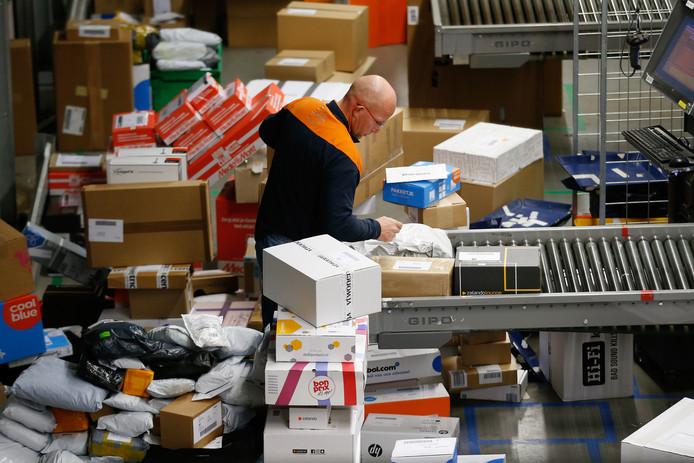 Een medewerker sorteert pakketjes in het sorteer- en distributiecentrum in Amersfoort.