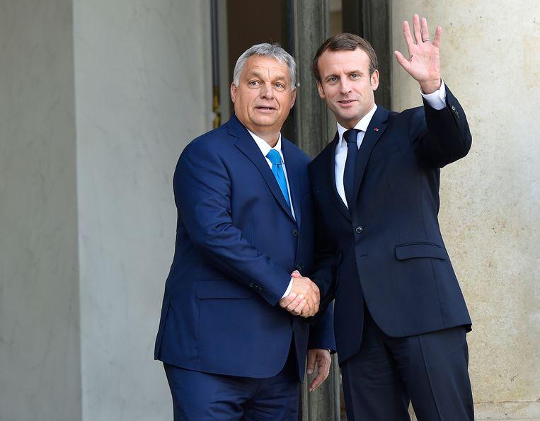 Macron (r) verwelkomt Orbán in het Élysée in Parijs, oktober 2019. Beeld Getty Images