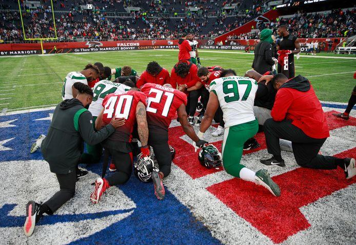 Spelers van Atlanta Falcons en New York Jets in een gezamenlijk gebed.
