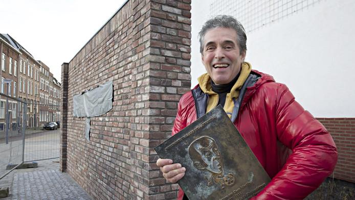 Kunstenaar Hans Citroen poseert met plaquette bij het nieuwe muurtje.