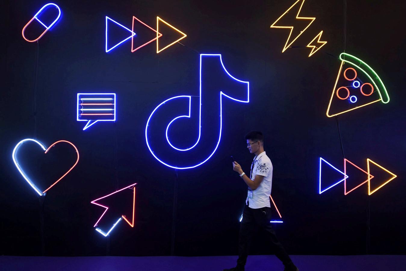 Een man loopt met zijn smartphone langs het logo van TikTok.