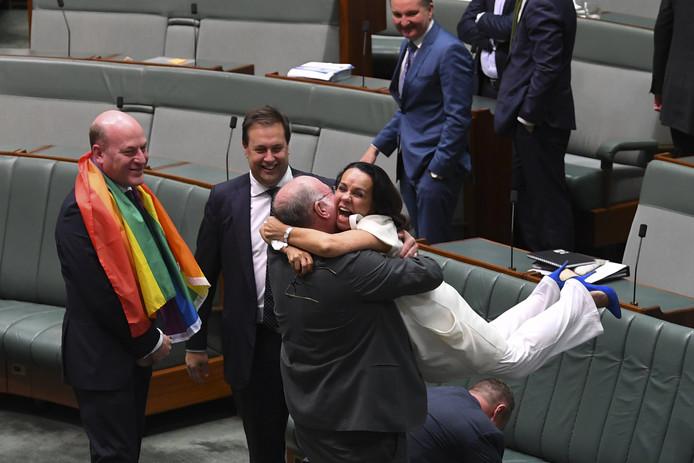 De Australische parlementsleden Warren Entsch en Linda Burney vieren het aannemen van de Homowet in het parlement in Canberra. Foto Lukas Coch