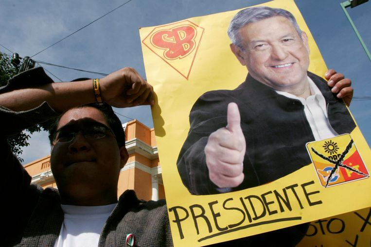 Een aanhanger van Andrés Manuel López Obrador met een poster van de nieuwe president. Beeld Photo News