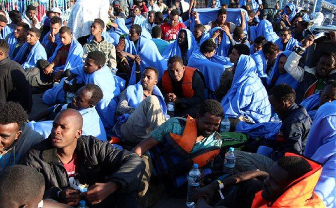 Een groep mannen is zojuist gered van hun gammele bootje op de Middellandse zee.