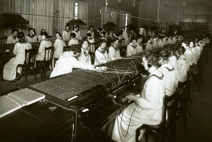 De telefooncentrale van Amsterdam in 1918. Medewerkers van de PTT verbinden bellers door.