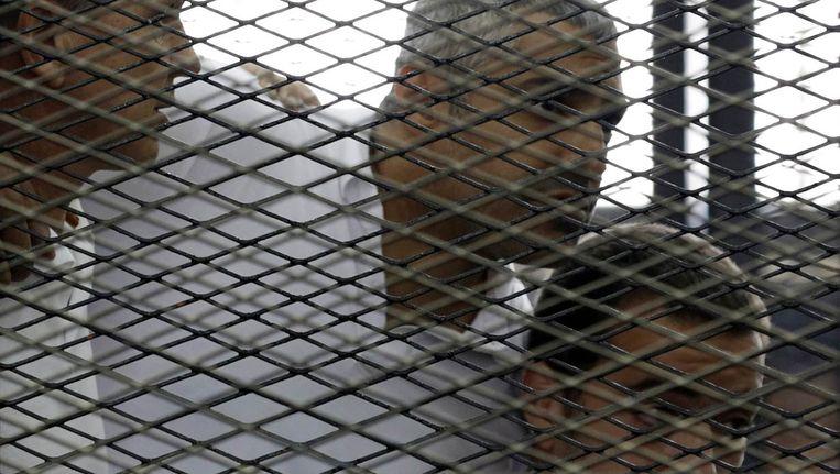 De drie journalisten van Al Jazeera Peter Greste, Mohamed Fahmy en Baher Mohamed luisteren naar de uitspraak van de Egyptische rechter in Caïro. Beeld reuters