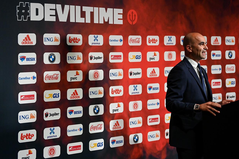 Bondscoach Roberto Martínez spreekt de pers toe. De wand achter hem toont hoeveel merken zich maar al te graag aan de nationale voetbalploeg linken.  Beeld BELGA