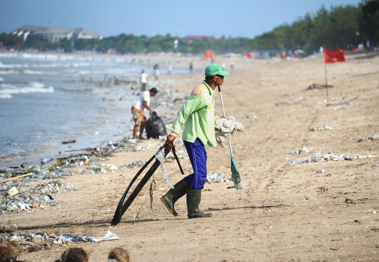 This photo taken on December 19, 2017 shows rubbish collectors clearing trash on Kuta beach near Denpasar, on Indonesia's tourist island of Bali. The palm-fringed shoreline of Bali's Kuta beach has long been a favourite with tourists seeking sun and surf, but nowadays its golden shores are being lost under a mountain of garbage. / AFP PHOTO / SONNY TUMBELAKA / TO GO WITH Indonesia-rubbish-Bali-environment,FEATURE by Bagus Saragih Beeld AFP