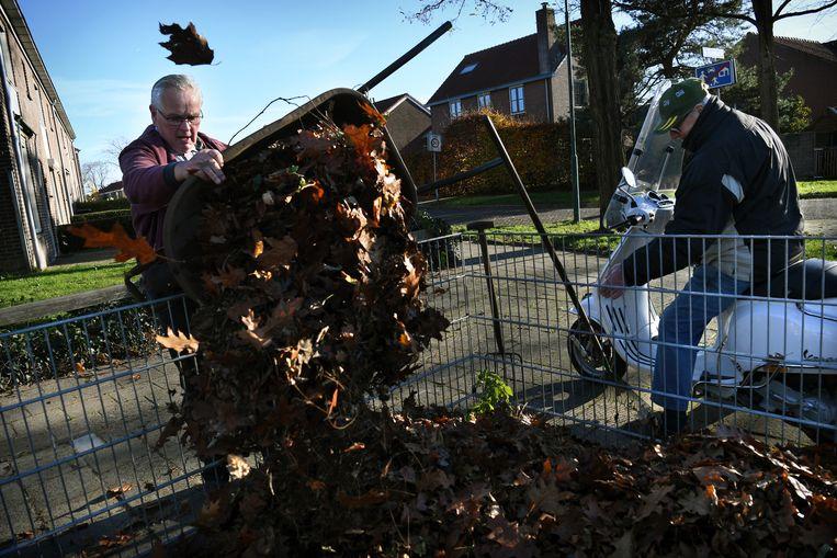 Een man gooit bladeren in de bladkorf. Beeld Marcel van den Bergh