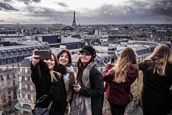Toeristen bekijken Parijs vanaf het panoramadak van het warenhuis Galeries Lafayette Paris Haussmann.