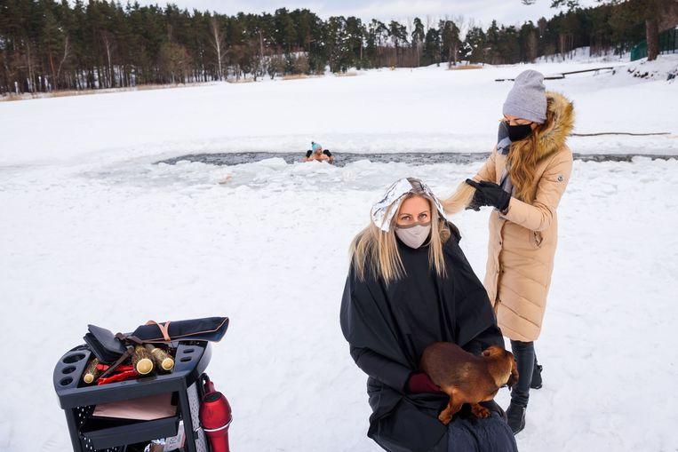 Een kapper heeft haar kapsalon verplaatst naar het bevroren meer van Babelitis, in Riga, Letland. Op de achtergrond neemt een ijszwemmer een duik.  Beeld AFP