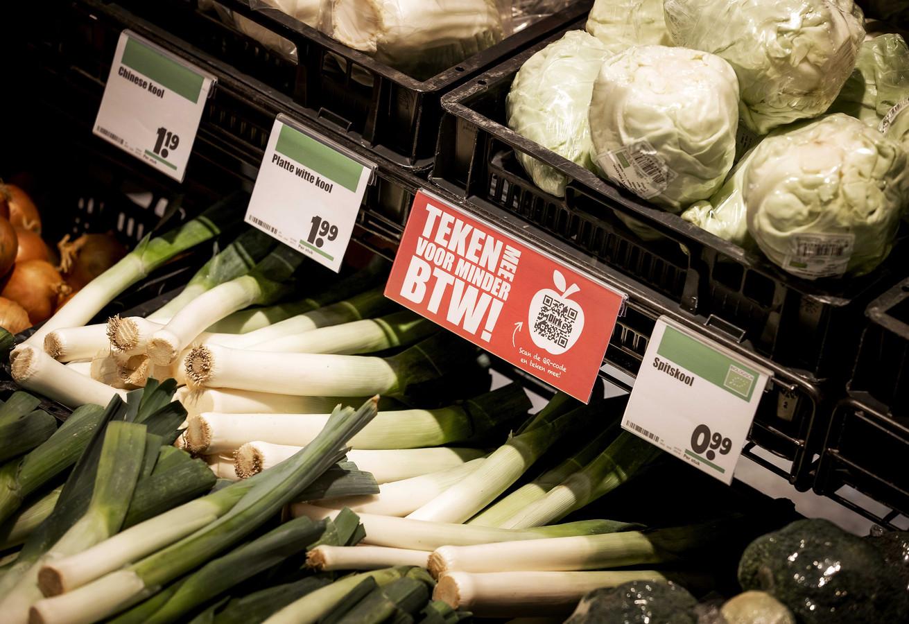 Een actie bordje voor minder btw tussen het groente en fruit van supermarktketen Dirk van den Broek. De supermarktketen start een online petitie om de belasting op groente en fruit te verlagen.