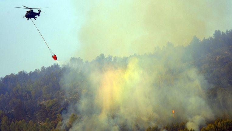 Een helikopter wordt ingezet om de bosbranden onder controle te krijgen. Beeld afp