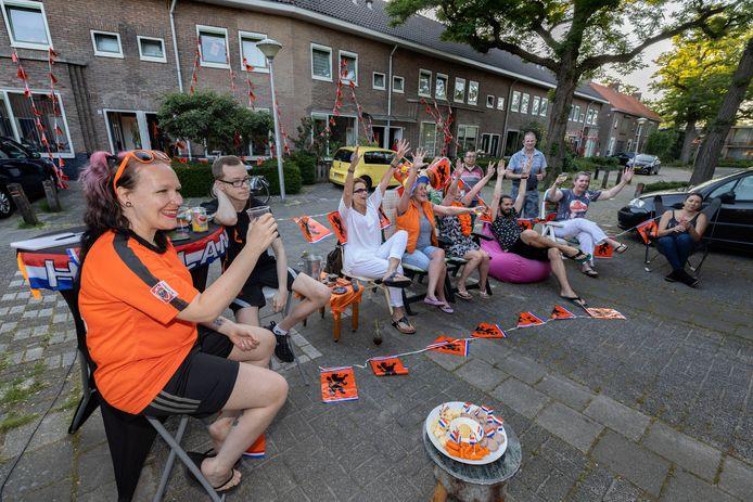 Bewoners van de Heggenroosstraat in Eindhoven (Stratum) kijken gezamenlijk op straat naar het voetballen