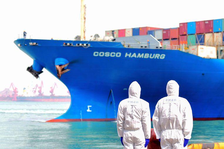 Werknemers in beschermende pakken kijken naar een containerschip in de haven van de Chinese stad Qingdao. Beeld AP