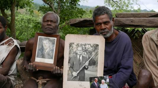 Dorpshoofd Jack Malia (rechts) toont beelden van de vereerde prins.