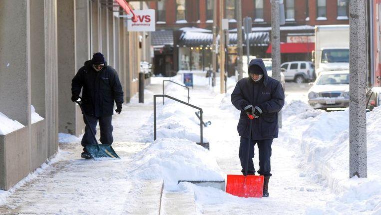 Een stoep in Boston wordt sneeuwvrij gemaakt. Bij een winterstorm in het noordoosten van de Verenigde Staten is op sommige plekken tot wel 60 centimeter sneeuw gevallen. Beeld anp