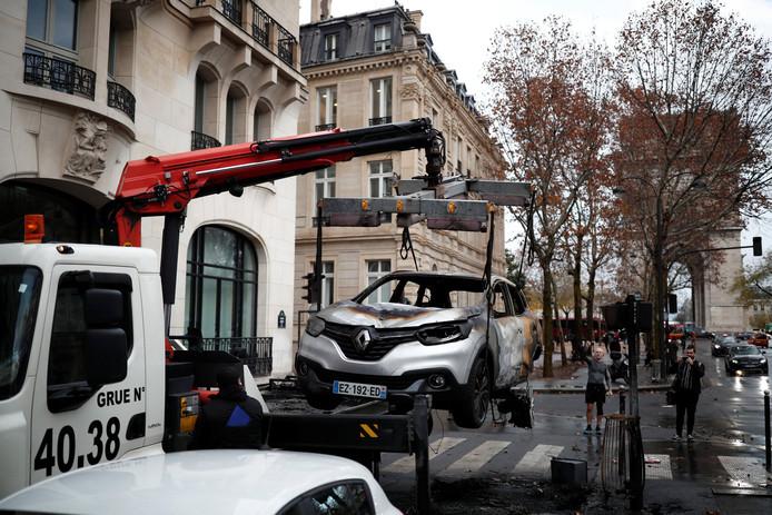 Een uitgebrande auto vlakbij de Arc de Triomphe wordt afgevoerd.
