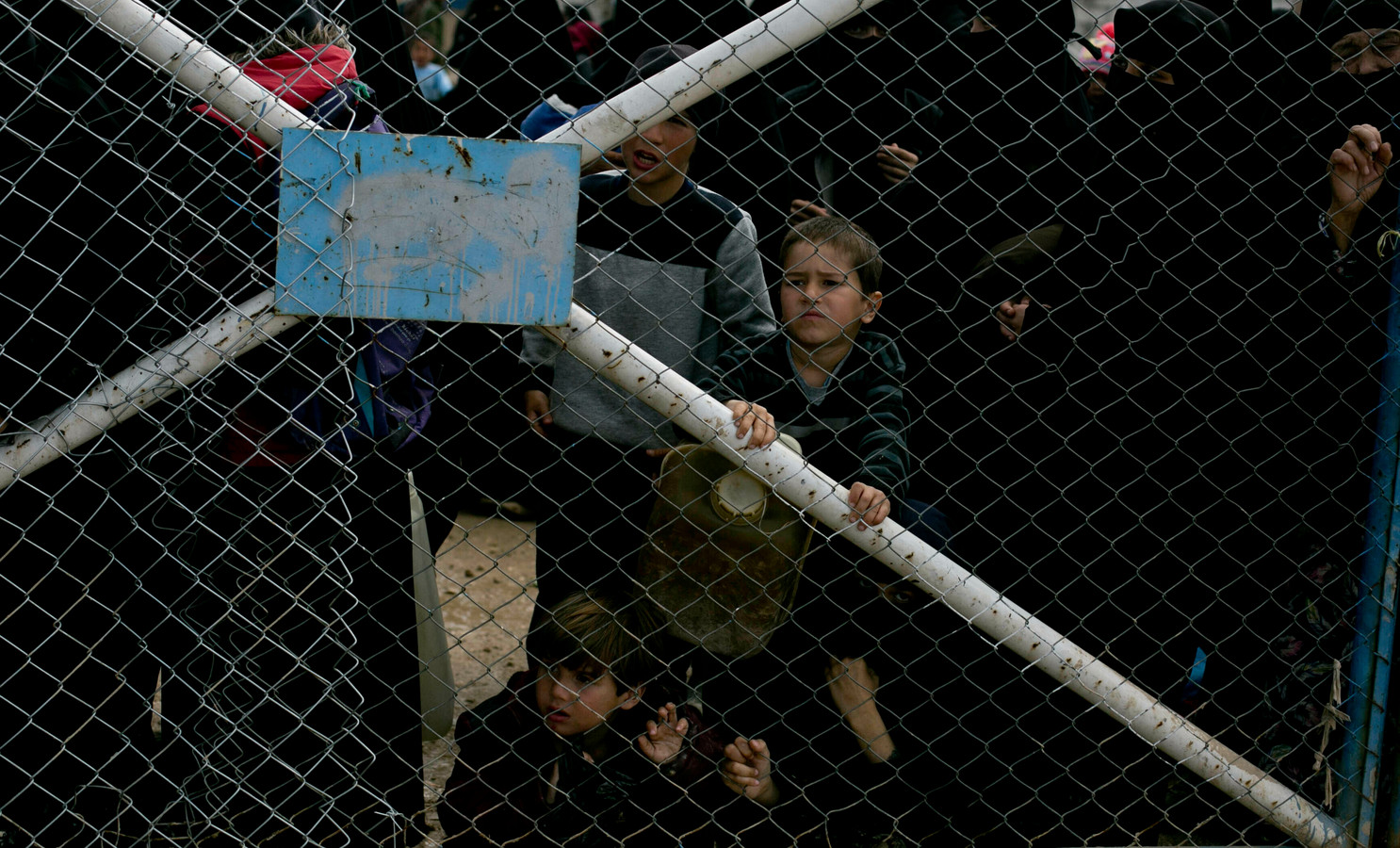 Kinderen kijken door het hek, waarmee het deel voor buitenlandse IS-vrouwen in het kamp Al Hol wordt afgesloten.