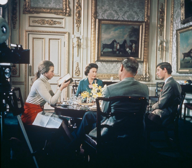 Koningin Elizabeth (tweede van links) luncht met haar gezin: prinses Anne, prins Philip en prins Charles (vlnr) op Windsor Castle in 1968, tijdens het filmen van de documentaire, waarvoor de Britse koninklijke familie een jaar lang werd gevolgd. Beeld Getty Images