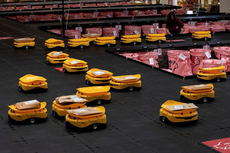 De Griekse post heeft er een gele vloot bij: robots moeten het sorteren van pakketten versnellen in Kryoneri, ten noorden van Athene. Beeld REUTERS