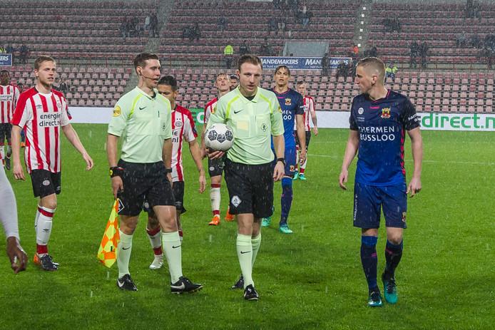 Scheidsrechter Stan Teuben (midden) staakt Jong PSV - Go Ahead Eagles vanwege het onweer.