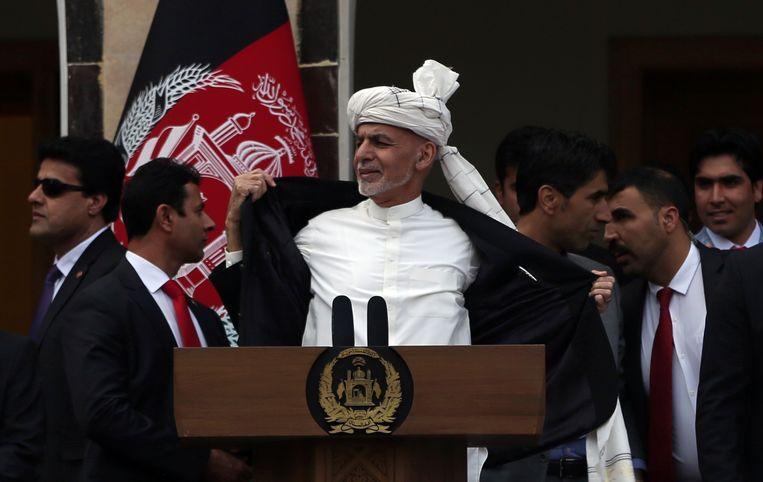 De Afghaanse president Ashraf Ghani trekt tijdens zijn beëdiging zijn jasje open om te laten zien dat hij geen kogelwerend vest draagt. Beeld AP