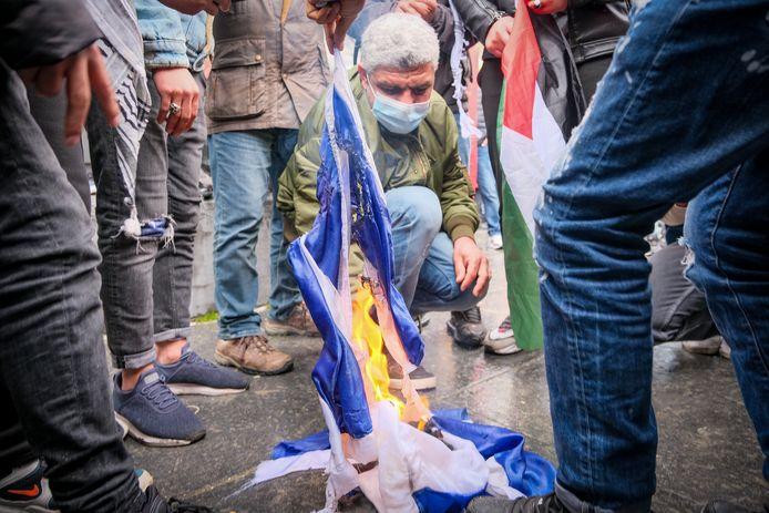 Betogers trappen op een Israëlische vlag en steken deze in brand.