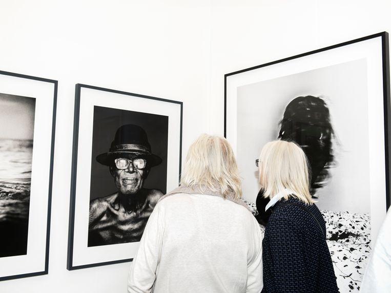 Bezoekers bekijken in 2016 foto's in de stand van Kahmann Gallery op een kunstbeurs in Amsterdam. Beeld Sanne De Wilde